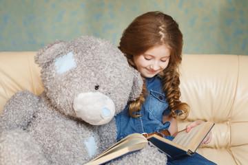 Cute little girl reading  with teddy bear