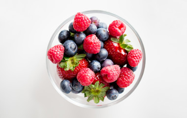 close up of summer berries in glass bowl