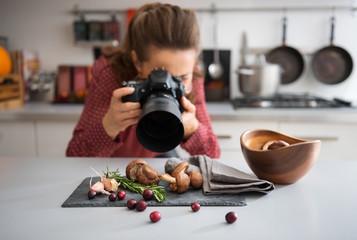Woman food photographer taking closeup of mushrooms Fotobehang