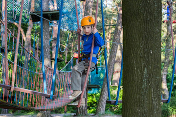 boy  climbing in adventure park,  rope park