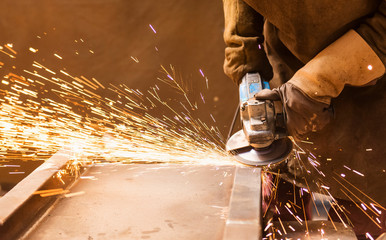 Young man in protective workwear welding in a factory