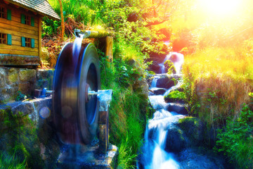 Dreamy water mill with a stream in mountain forest.