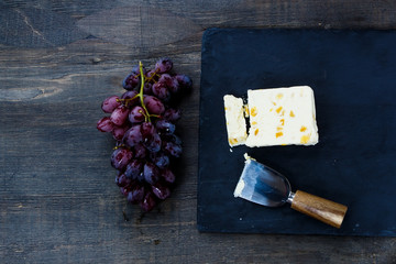 Cheese and grape on dark wooden background.