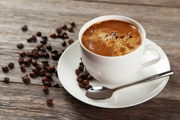 Cup of coffee with coffee beans on grey wooden background