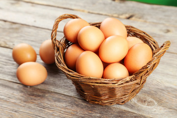 Chicken eggs in basket on grey wooden background