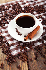 Cup of coffee with cinnamon on brown wooden background