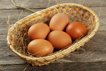 Eggs in basket on grey wooden background
