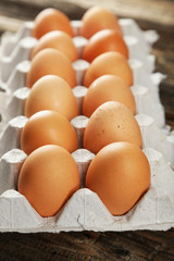 Eggs in the package on brown wwoden background
