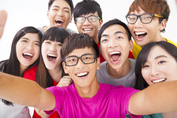 group of smiling friends with camera  taking self photo