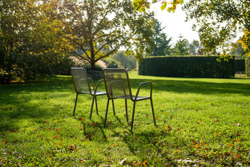 Empty metal chairs among fresh greenery in a park