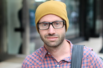 Portrait of a hipster wearing glasses and a hat with urban background