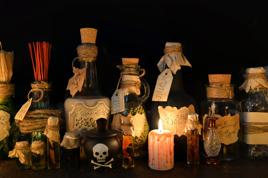 Halloween still life with witch bottles and bloody candle