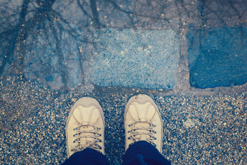 Puddle reflection with retro filter effect. View from above