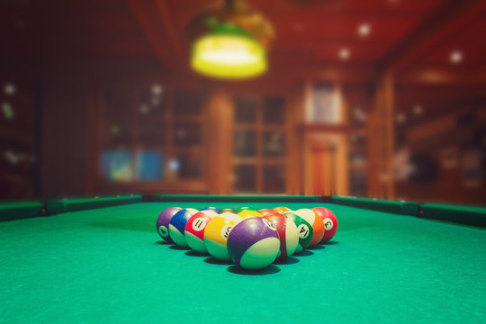 Billiard balls on green pool table in bar or pub