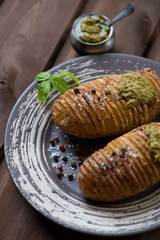 Close-up of hasselback potatoes served with pesto sauce