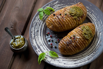 Baked hasselback potatoes on a plate with basil pesto, close-up