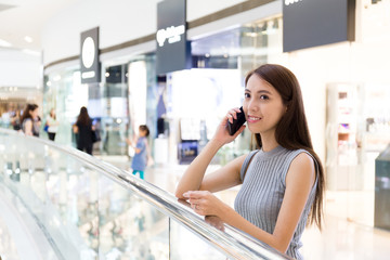 Young lady talk to cellphone at shopping mall
