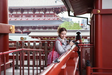 Caucasian woman tourist walks with camera in Japanese temple
