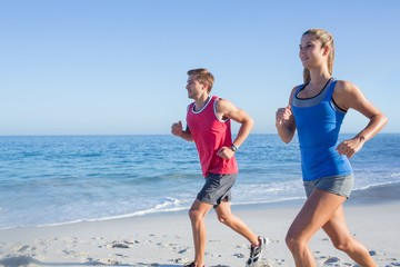 Happy couple running together beside the water