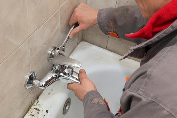 Plumber works in a bathroom fixing, placing faucet