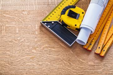 Blueprints square ruler tape measure and wooden meter on oak boa