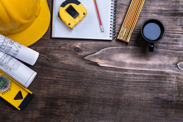 Copybook pencil cup of coffee and construction objects on pine w