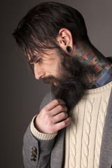 young man with a long beard and tatoos posing in the studio