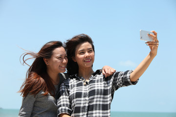 Woman take photo by smartphone herself with her friend