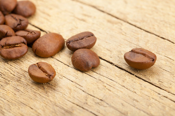 Coffee beans on old wooden table - close up studio shot