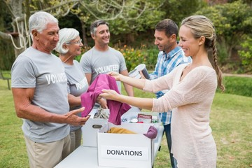 Happy volunteer family separating donations stuffs