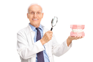 Dentist holding denture and a magnifying glass