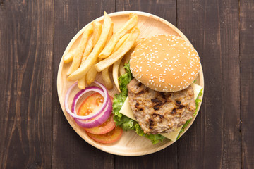 BBQ hamburgers with french fries on wooden background.