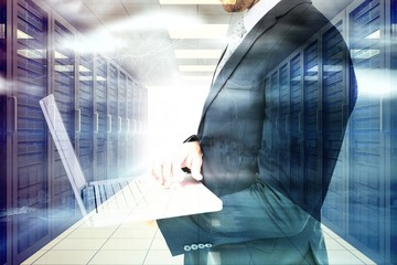 Composite image of businessman holding laptop