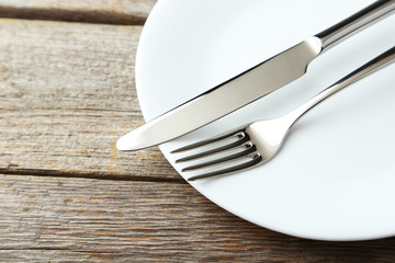 Fork, knife and plate on grey wooden background