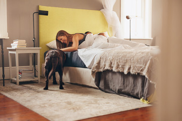 Woman lying on bed playing with her pet dog in morning