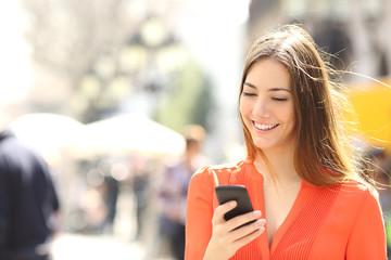 Woman wearing orange shirt texting on the smart phone