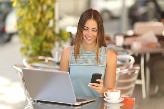 Entrepreneur working with a phone and laptop in a coffee shop