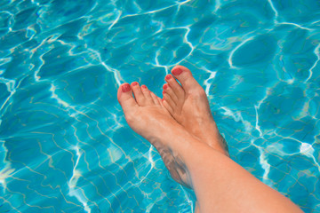 Woman feet at the swimming pool, turquoise blue water