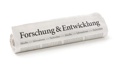 Zeitungsrolle mit der Überschrift Forschung und Entwicklung