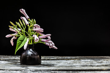 Flowers in a vase on a wooden  after dark.