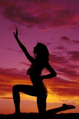 silhouette of a fit woman bikini kneel hand up