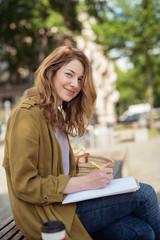 lächelnde junge frau sitzt auf einer bank und schreibt