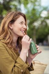 attraktive frau genießt einen grünen smoothie