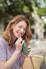 lachende frau mit einem grünen smoothie in der stadt