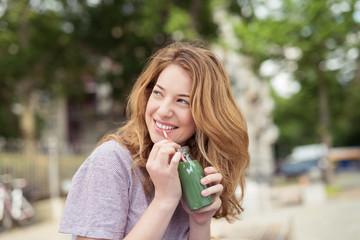 lachende junge frau trinkt einen grünen smoothie