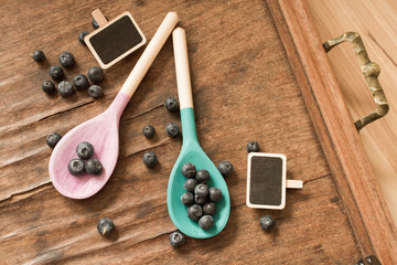 blueberries and wooden spoon on a wooden tray