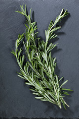 Bunch of Rosemary sitting on black slate.