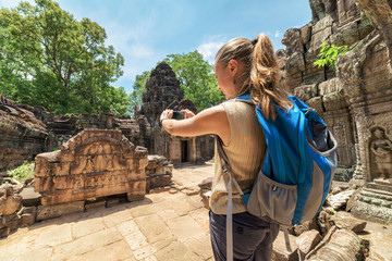 Tourist with smartphone in mysterious ruins of Angkor, Cambodia