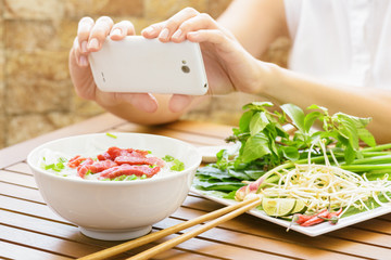 Young woman taking a picture the Pho Bo on smartphone in Vietnam