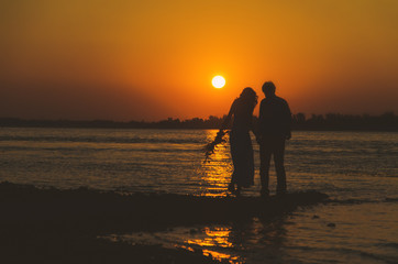 Young couple in love meet sunrise (sunset) on the coast
